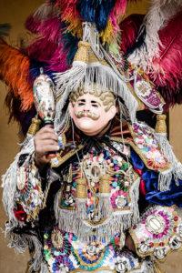 homme déguisé avec un masque et un chapeau à plumes pour la fête de Santo Tomas à Chichicastenango Guatemala